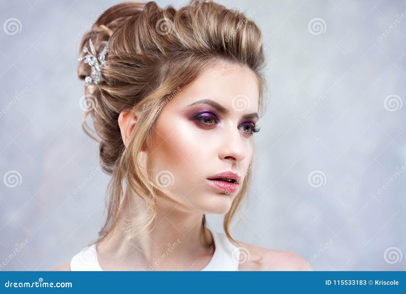 Giovane bella sposa con un alta pettinatura elegante Acconciatura di nozze con l accessorio in suoi capelli