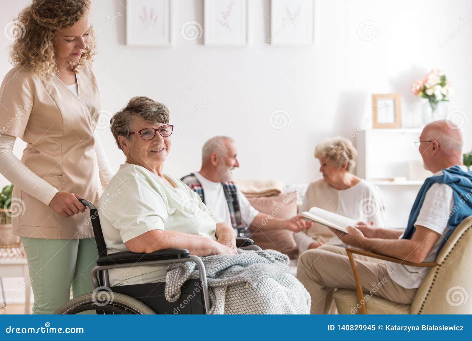Giovane bello badante e donna senior positiva che si siedono alla sedia a rotelle nella casa di cura per gli anziani