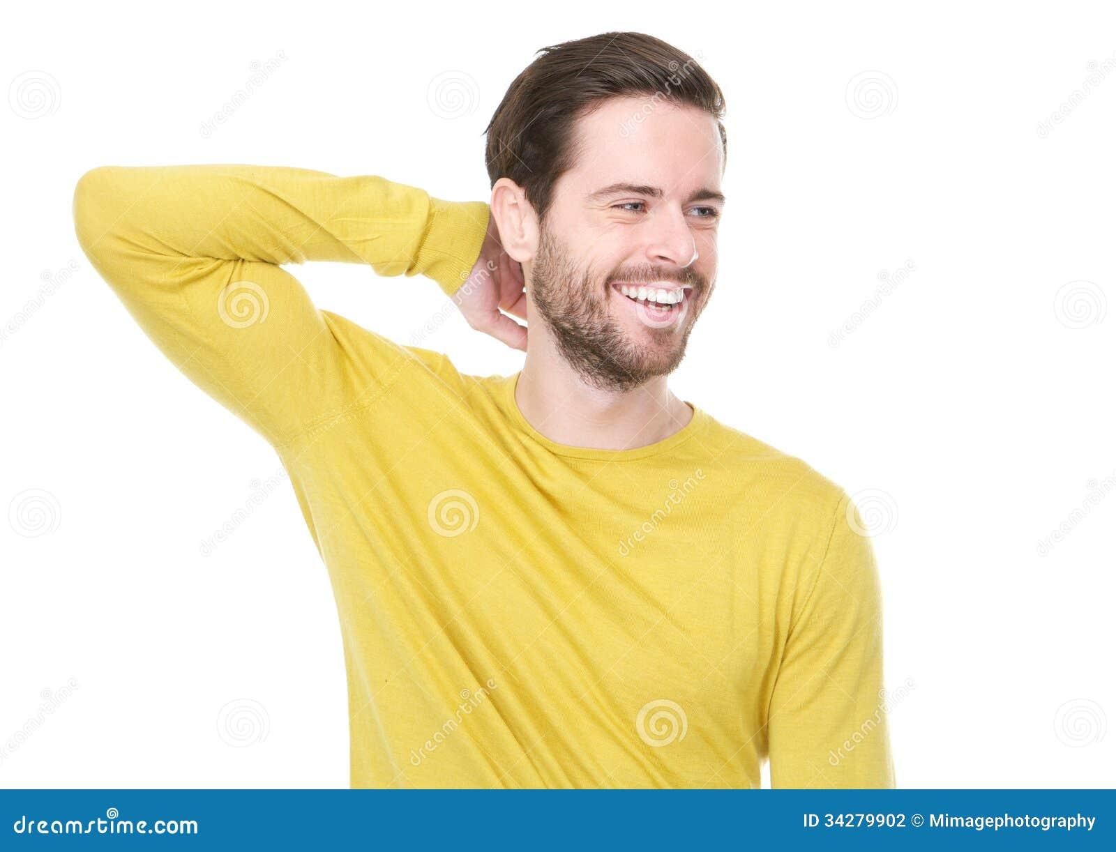 Giovane bello in camicia gialla che sorride con la mano in capelli