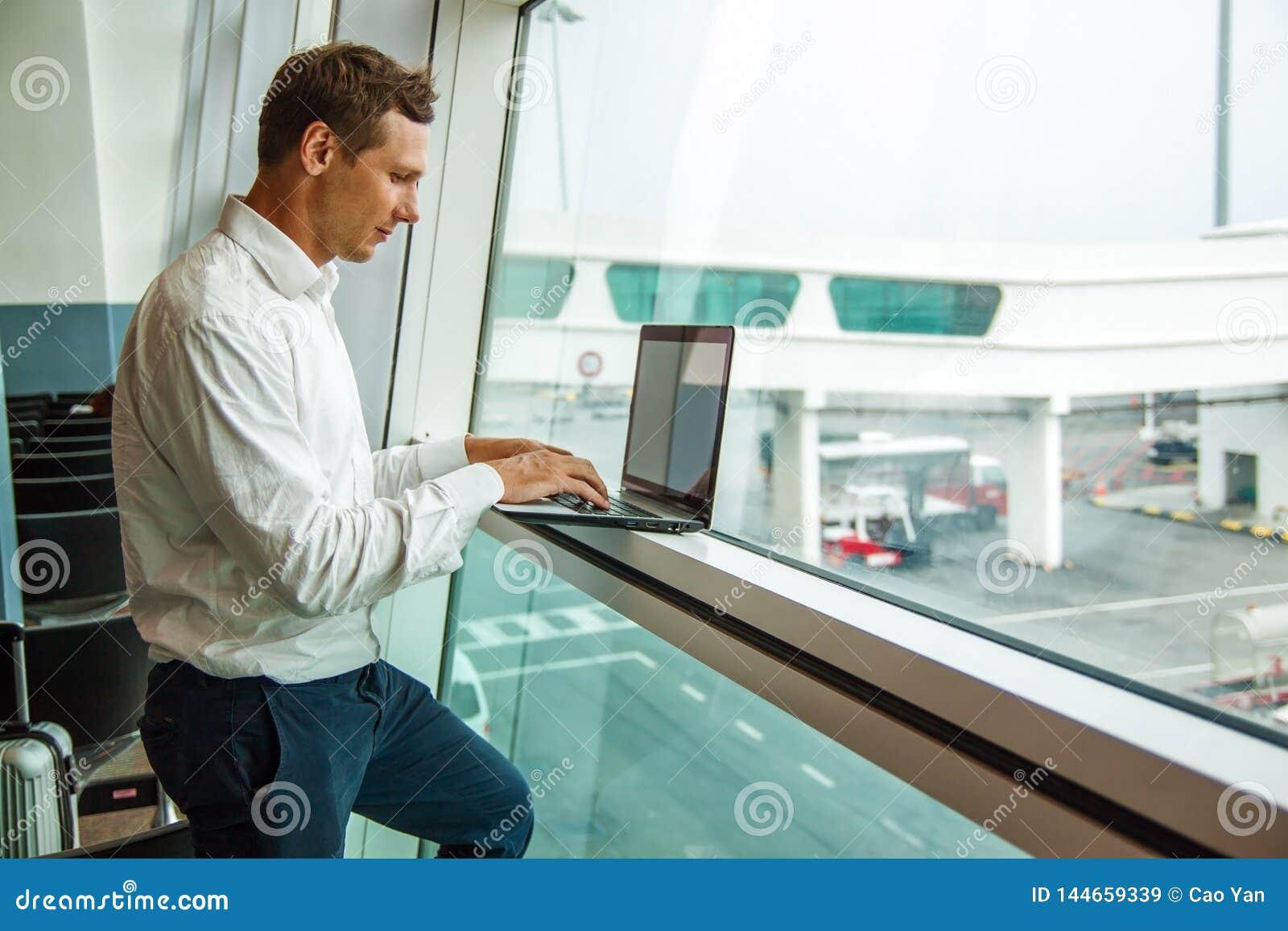 Giovane bello che lavora con il computer portatile in aeroporto quando aspettano il suo aereo
