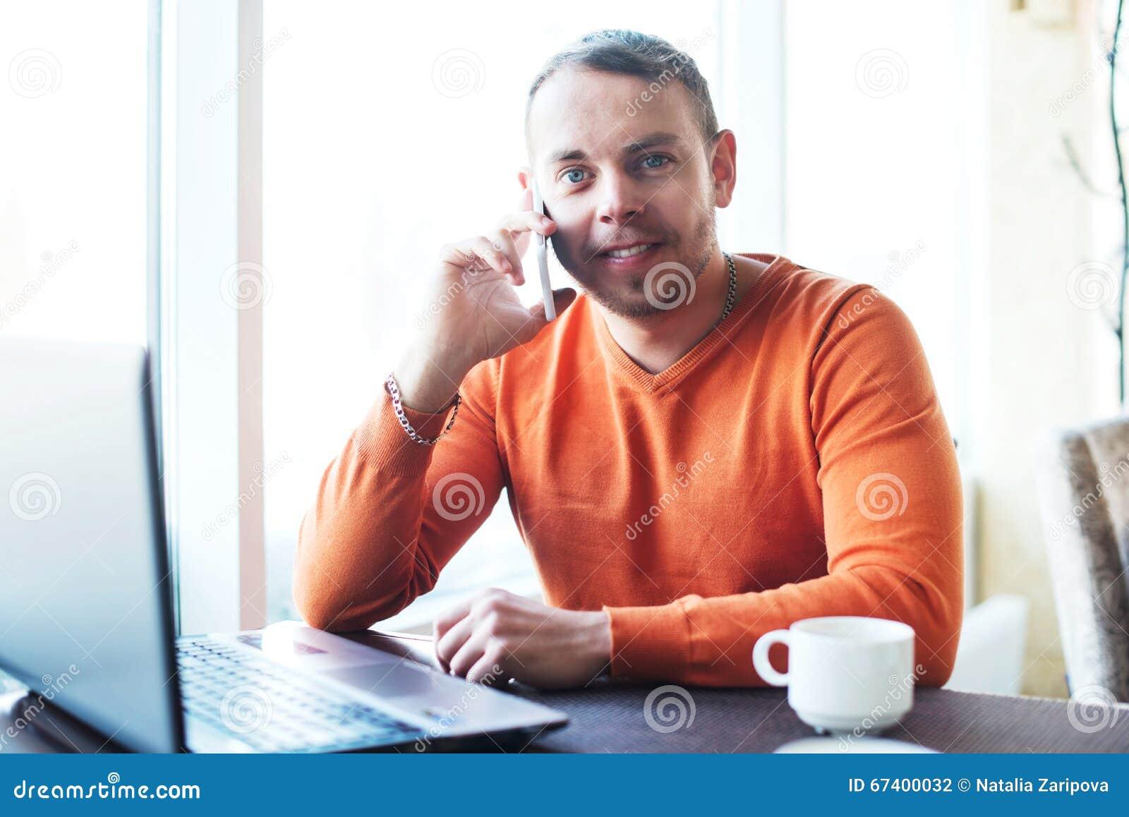 Giovane bello che lavora con il taccuino, parlando sul telefono, sorridere, esaminante macchina fotografica, mentre godendo del c