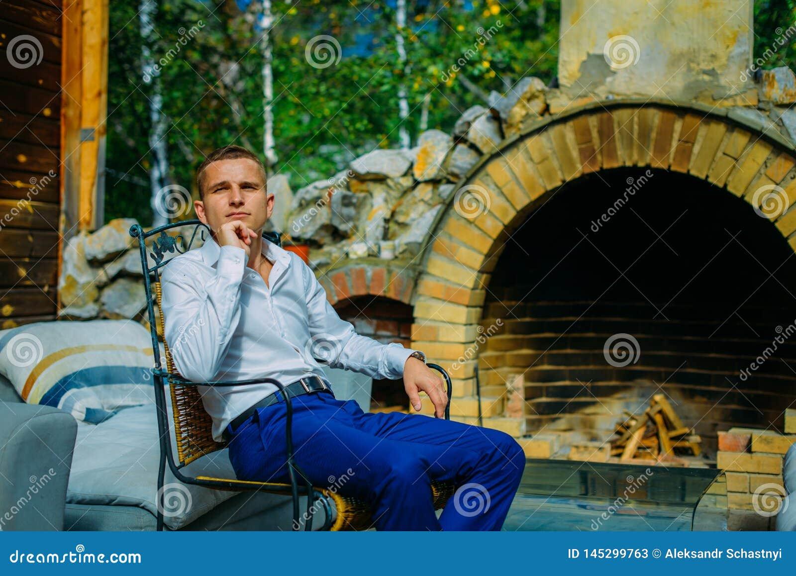 Giovane bello elegante che si siede dal camino in una veranda all aperto d annata