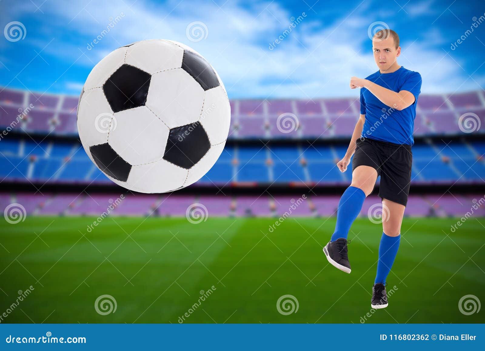 Giovane calciatore nella palla di respinta uniforme del blu sullo stadio