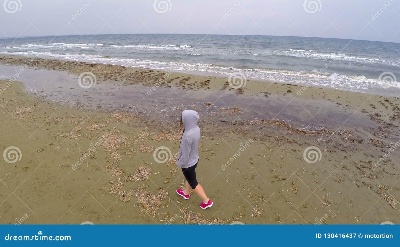Giovane camminata femminile sulla spiaggia e pensare alla vita, colpo aereo del fuco