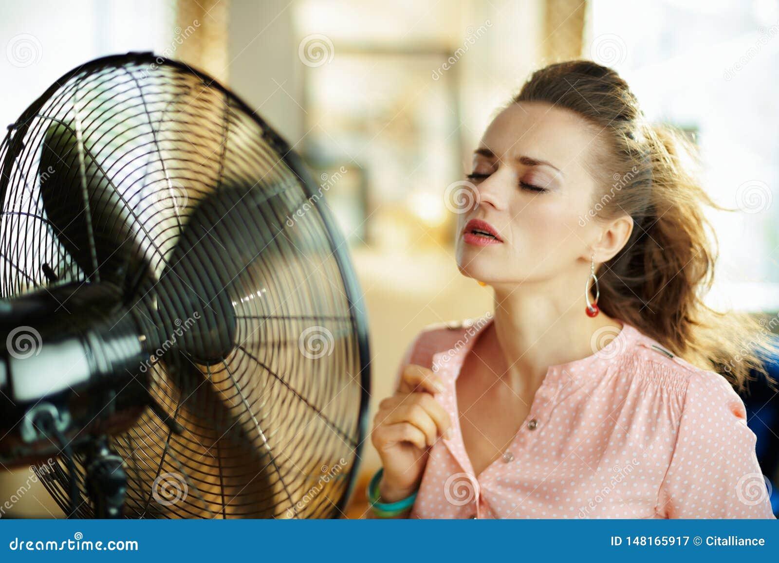 Giovane casalinga che gode della freschezza davanti al fan di lavoro