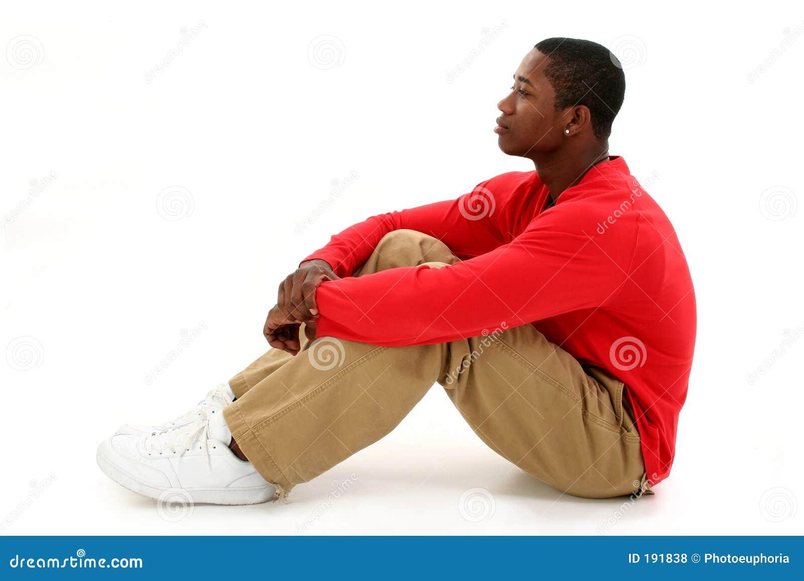 Giovane casuale che si siede sul pavimento