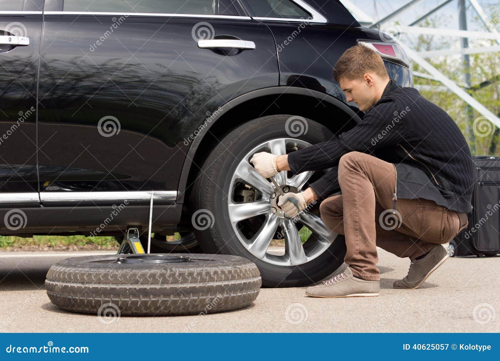 Giovane che cambia il pneumatico perforato sulla sua automobile
