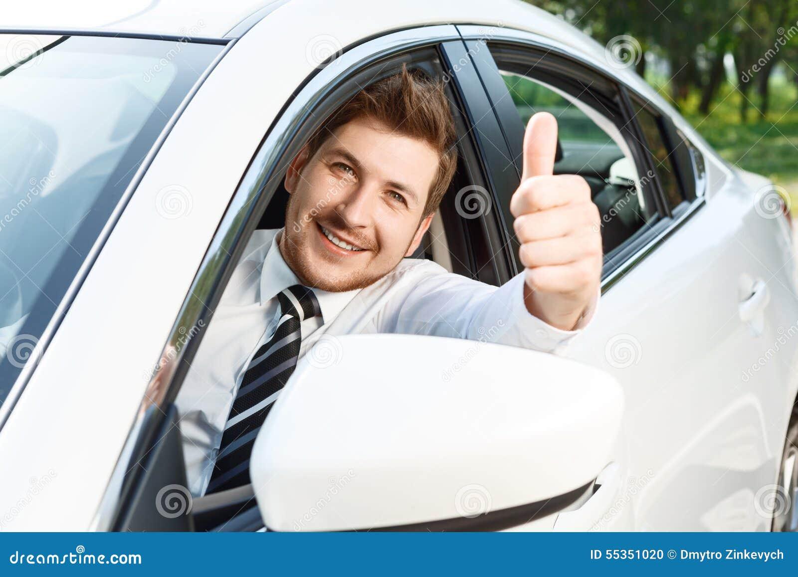 Giovane che fa i pollici su in automobile