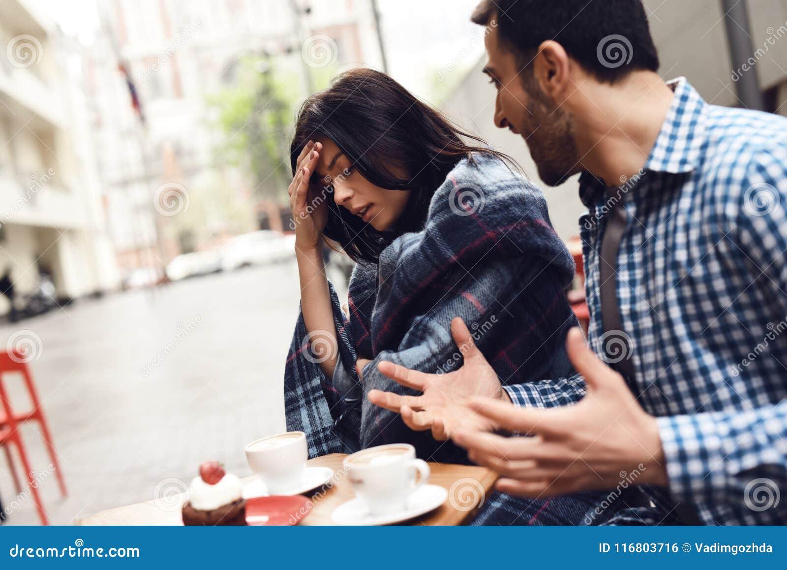 Giovane che grida alla ragazza alla tavola in caffè