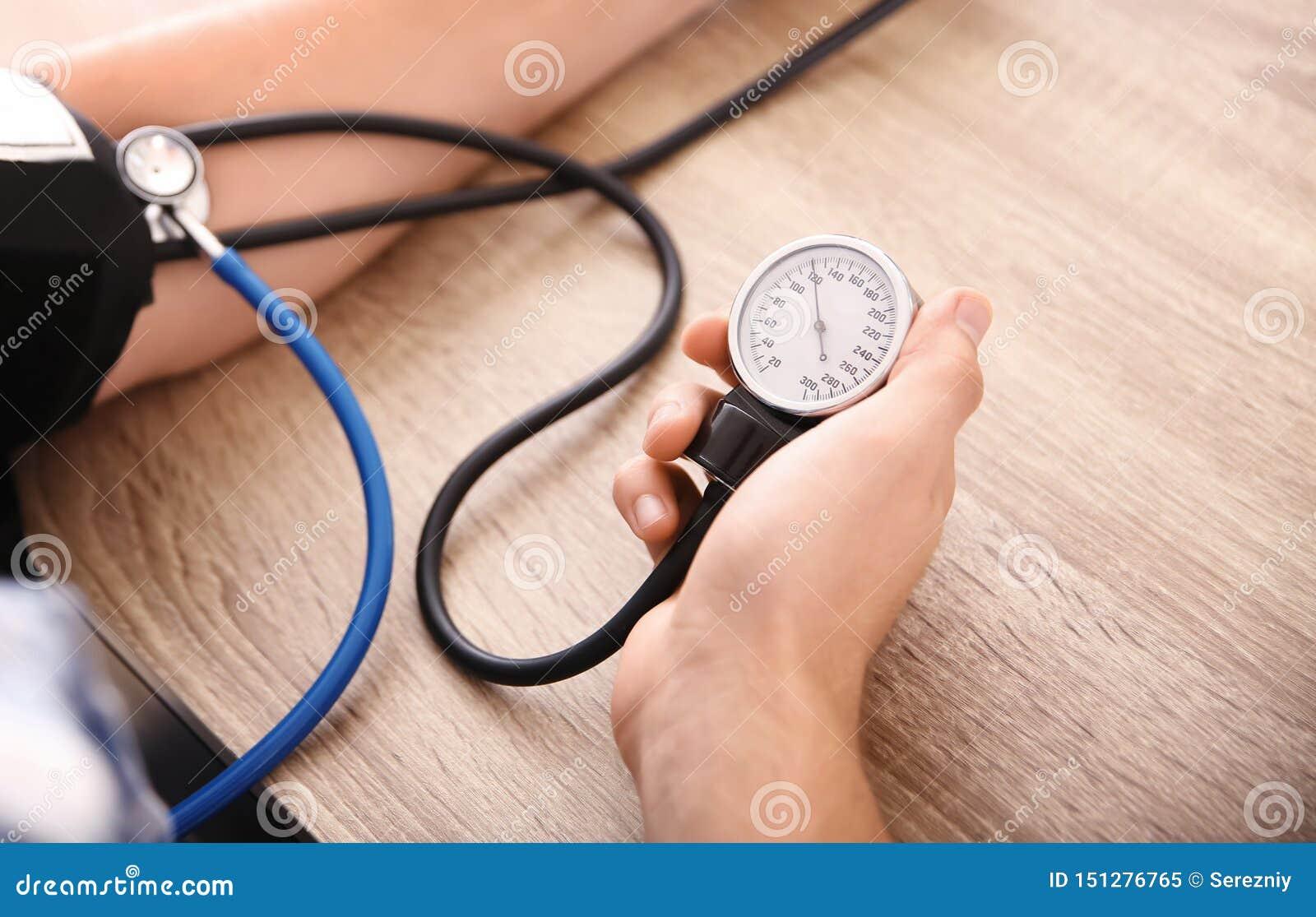 Giovane che misura la sua pressione sanguigna a casa