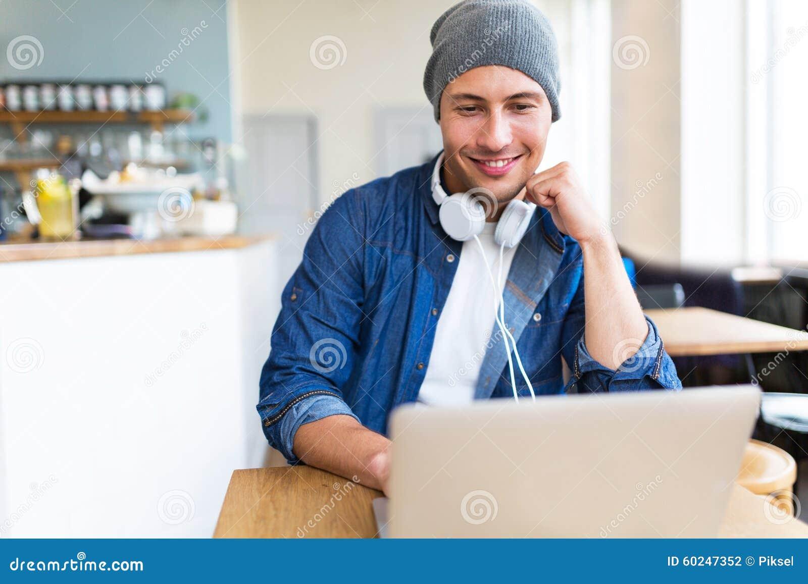 Giovane che per mezzo del computer portatile al caffè