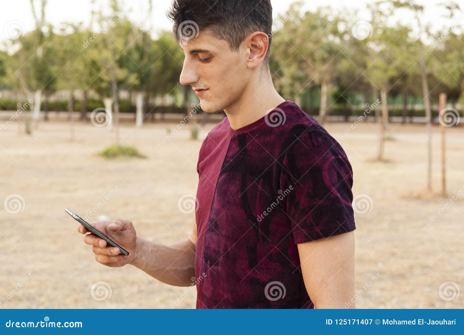 Giovane che per mezzo dello smartphone all aperto