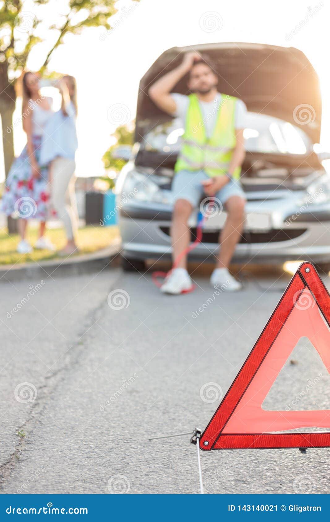 Giovane che ripara un automobile rotta dal lato della strada Fuoco selettivo sul triangolo di emergenza in priorità alta