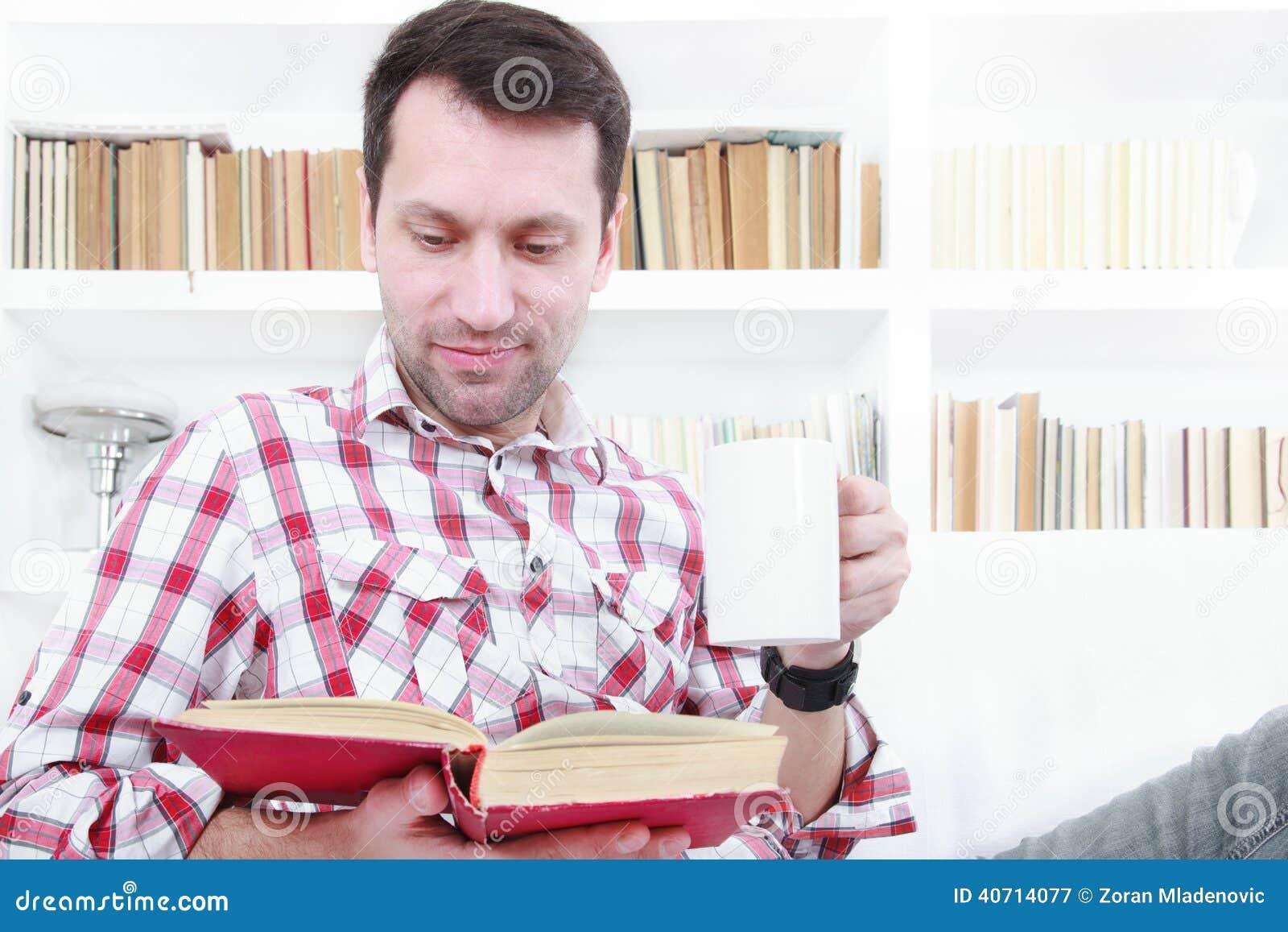Giovane che si rilassa sul libro di lettura dello strato e che gode del caffè