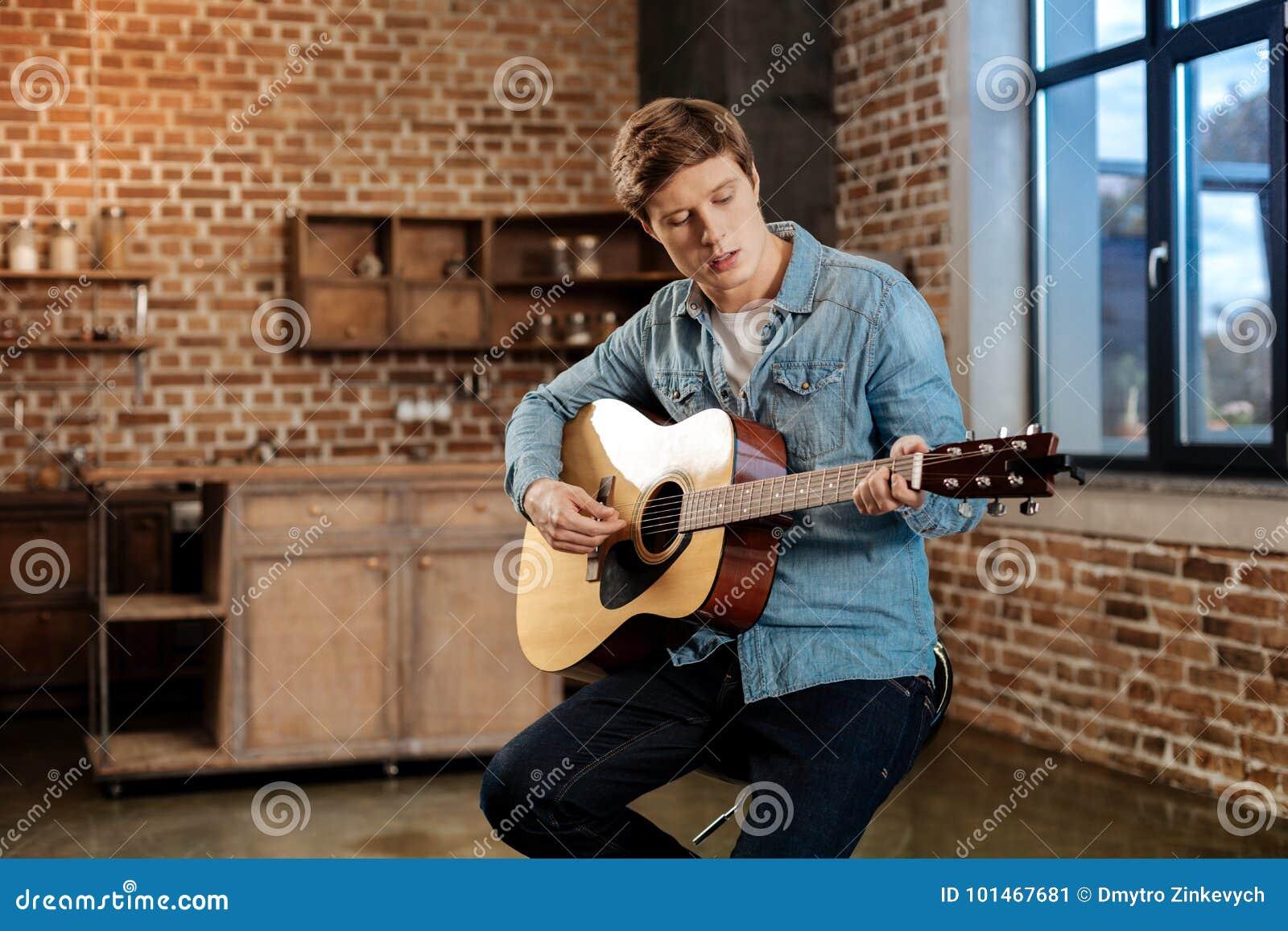 Giovane che si siede sullo sgabello da bar e che gioca chitarra