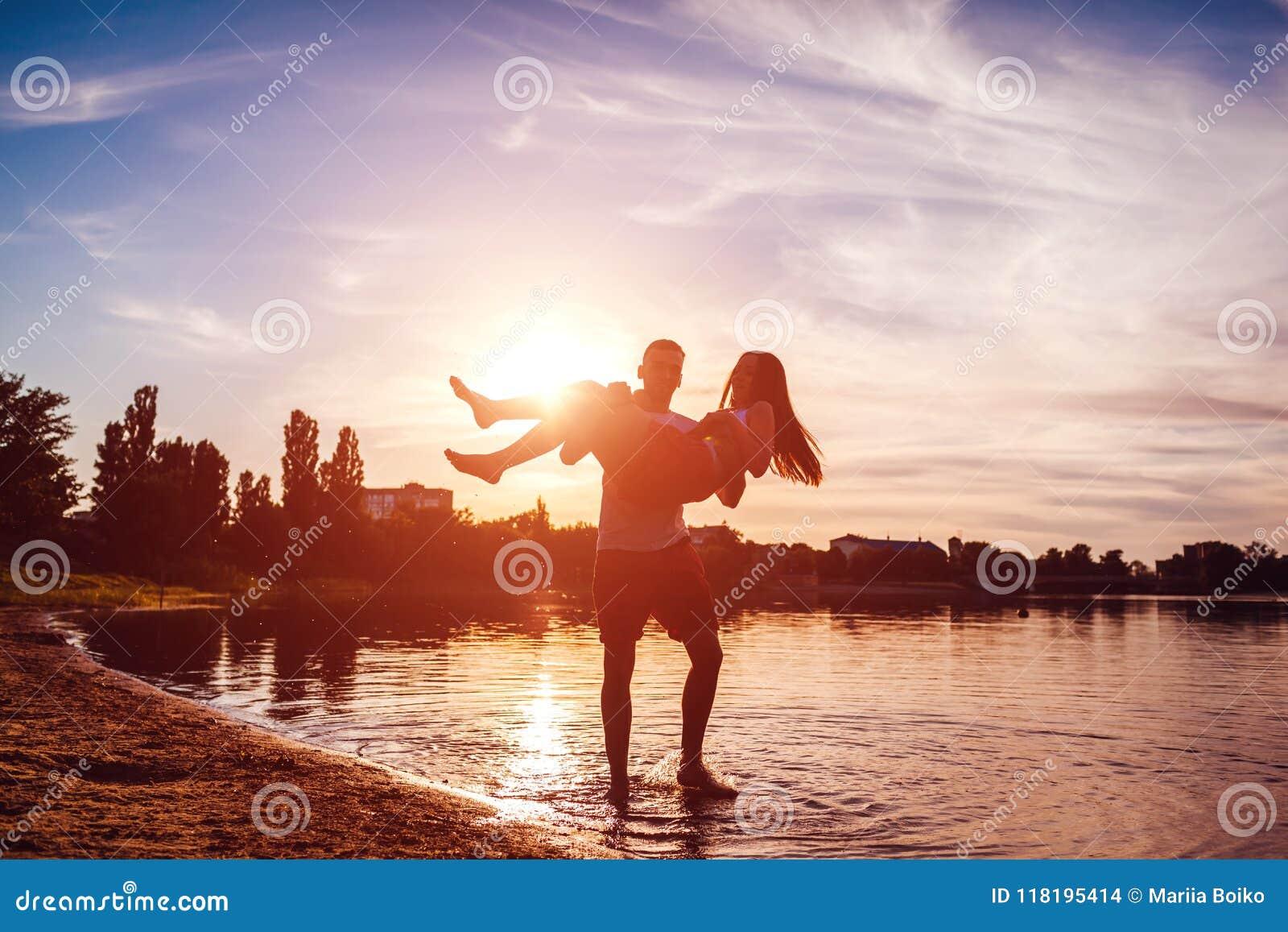 Giovane che tiene la sua amica in sue mani Coppie divertendosi sulla sponda del fiume di estate al tramonto Rilassamento dei tipi