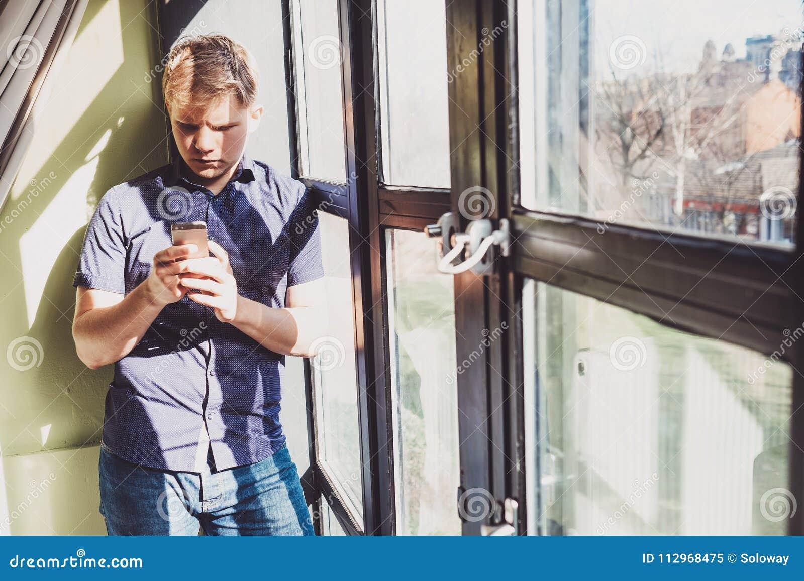 Giovane con il soggiorno del telefono cellulare vicino al giorno