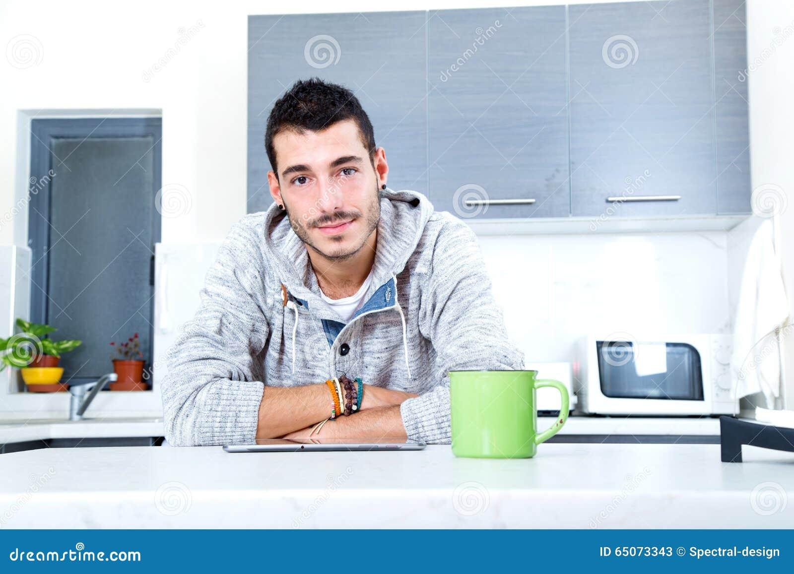 Giovane con la compressa nella cucina