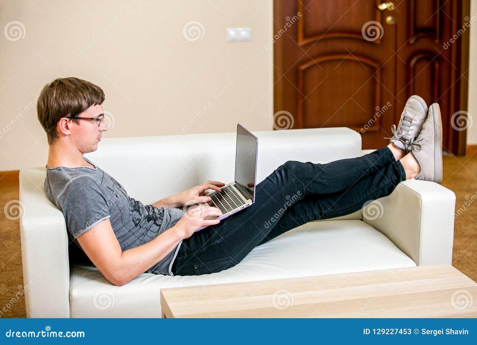 Giovane concentrato con funzionamento di vetro su un ufficio del computer portatile a casa Trovandosi sullo strato e scrivere su