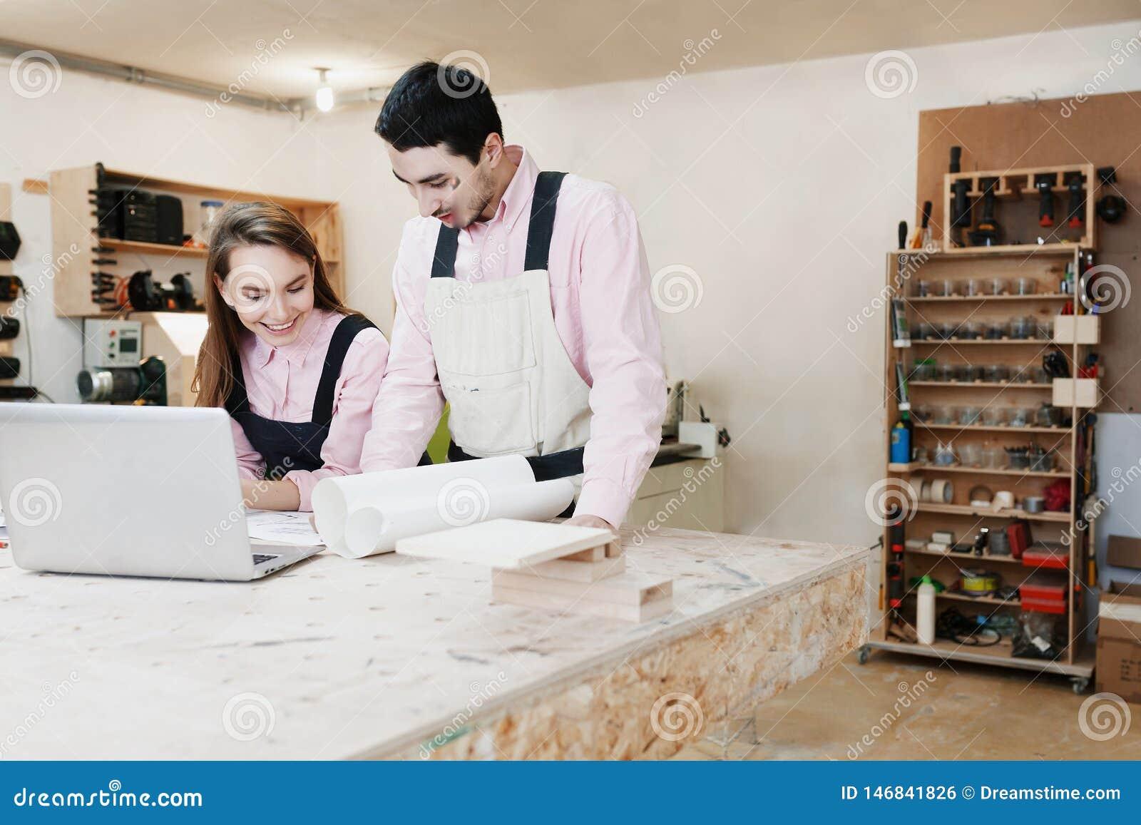 Giovane condizione felice della famiglia ad un banco da lavoro in un officina di carpenteria, scrivente un progetto r Giovane imp