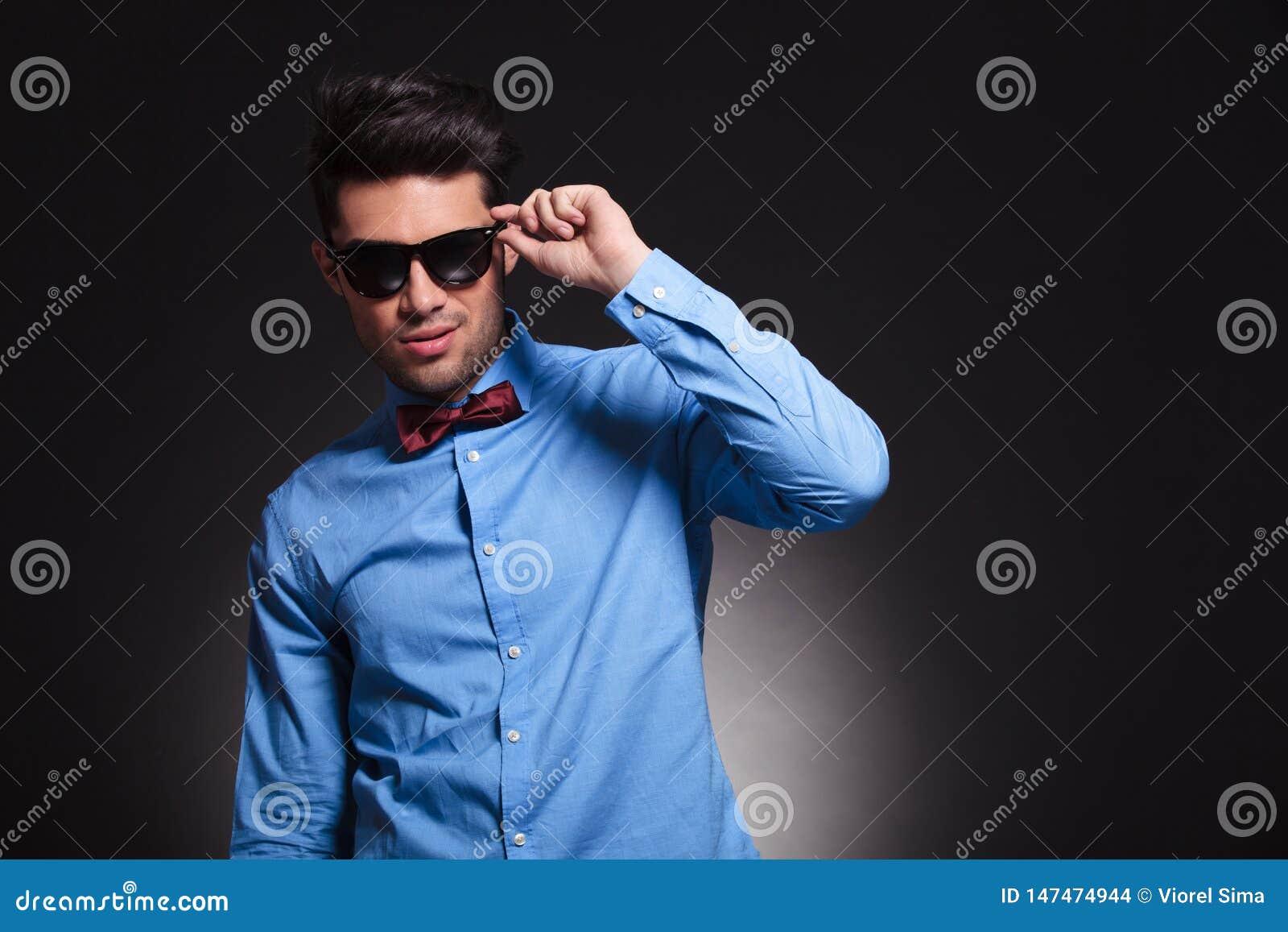Giovane condizione maschio incantante e riparare i suoi occhiali da sole