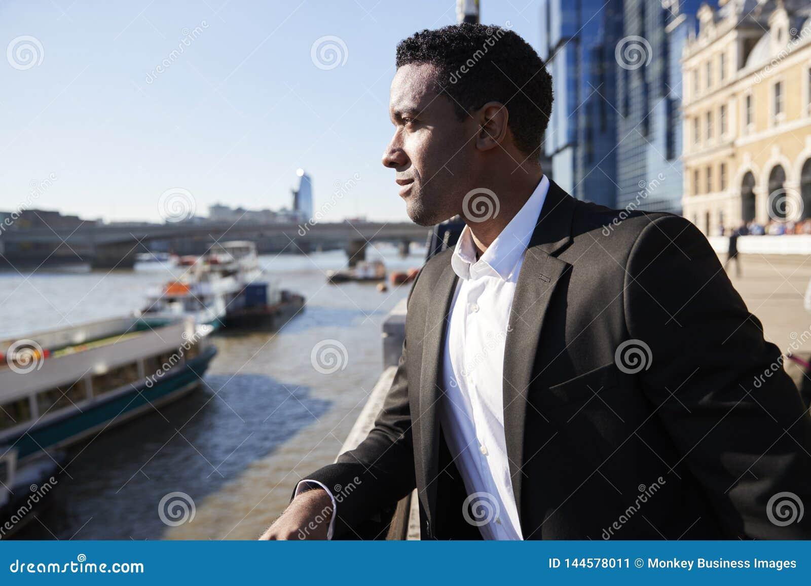 Giovane condizione posteriore dell uomo d affari alla riva del fiume di Tamigi nella città di Londra che ammira la vista, fine su
