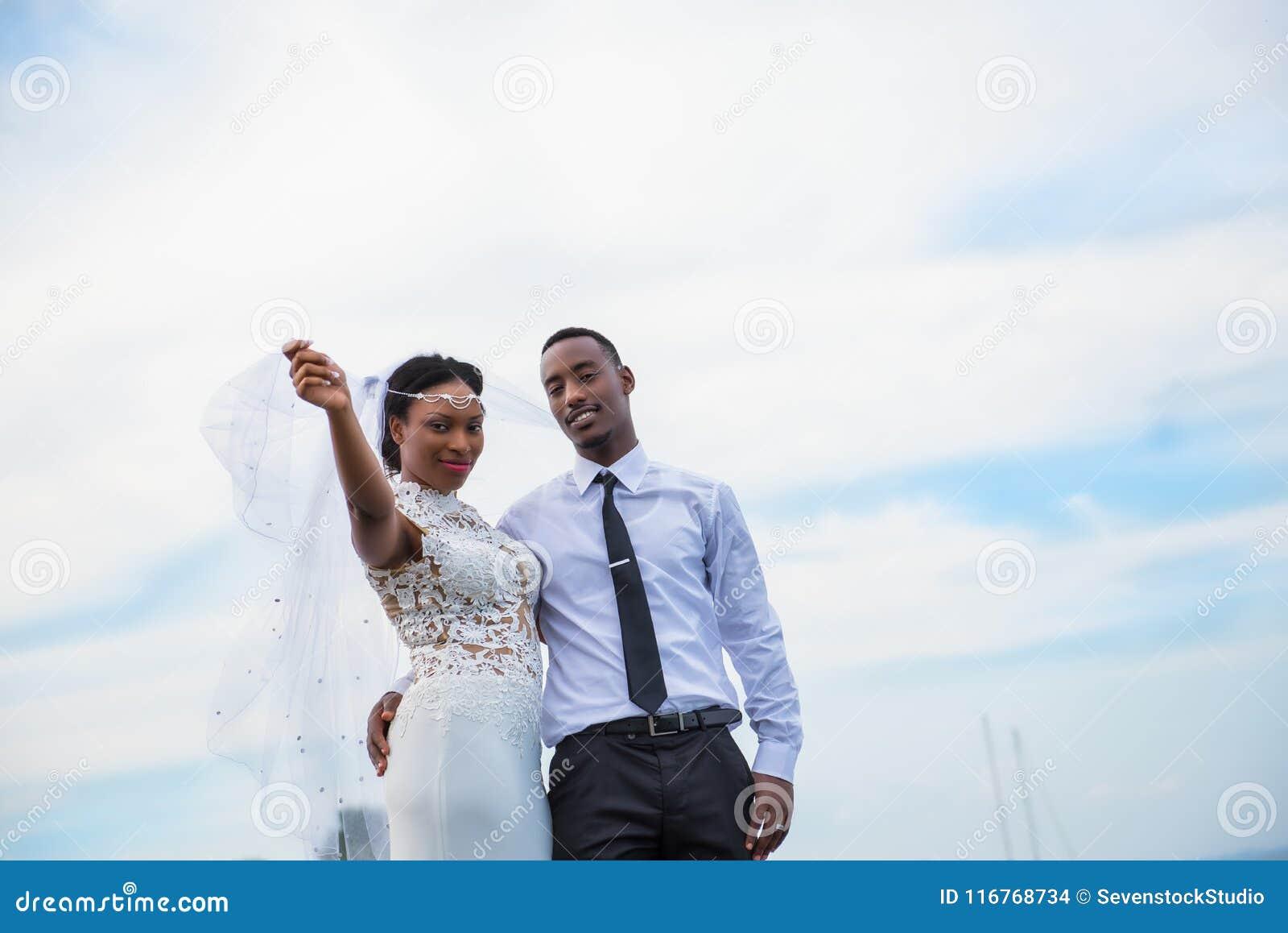 Giovane coppia sposata che posa all aperto con il cielo nel fondo