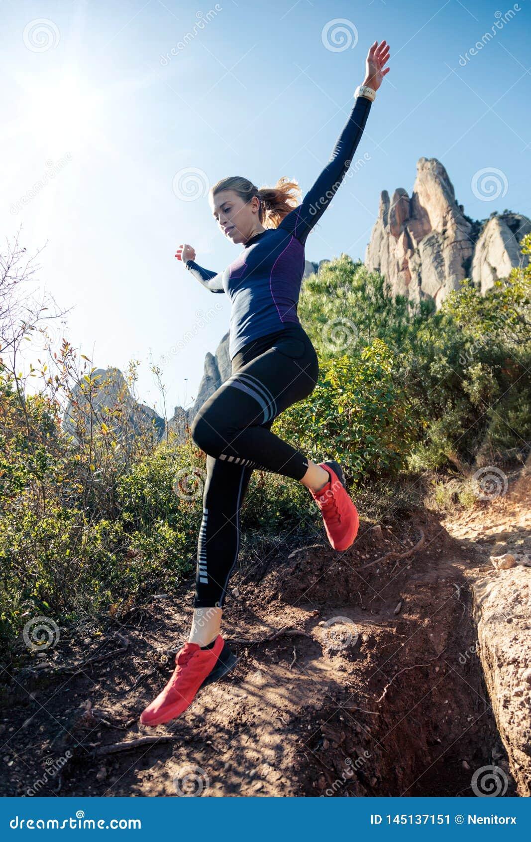 Giovane corridore della traccia della donna di forma fisica che corre e che salta sulla montagna rocciosa
