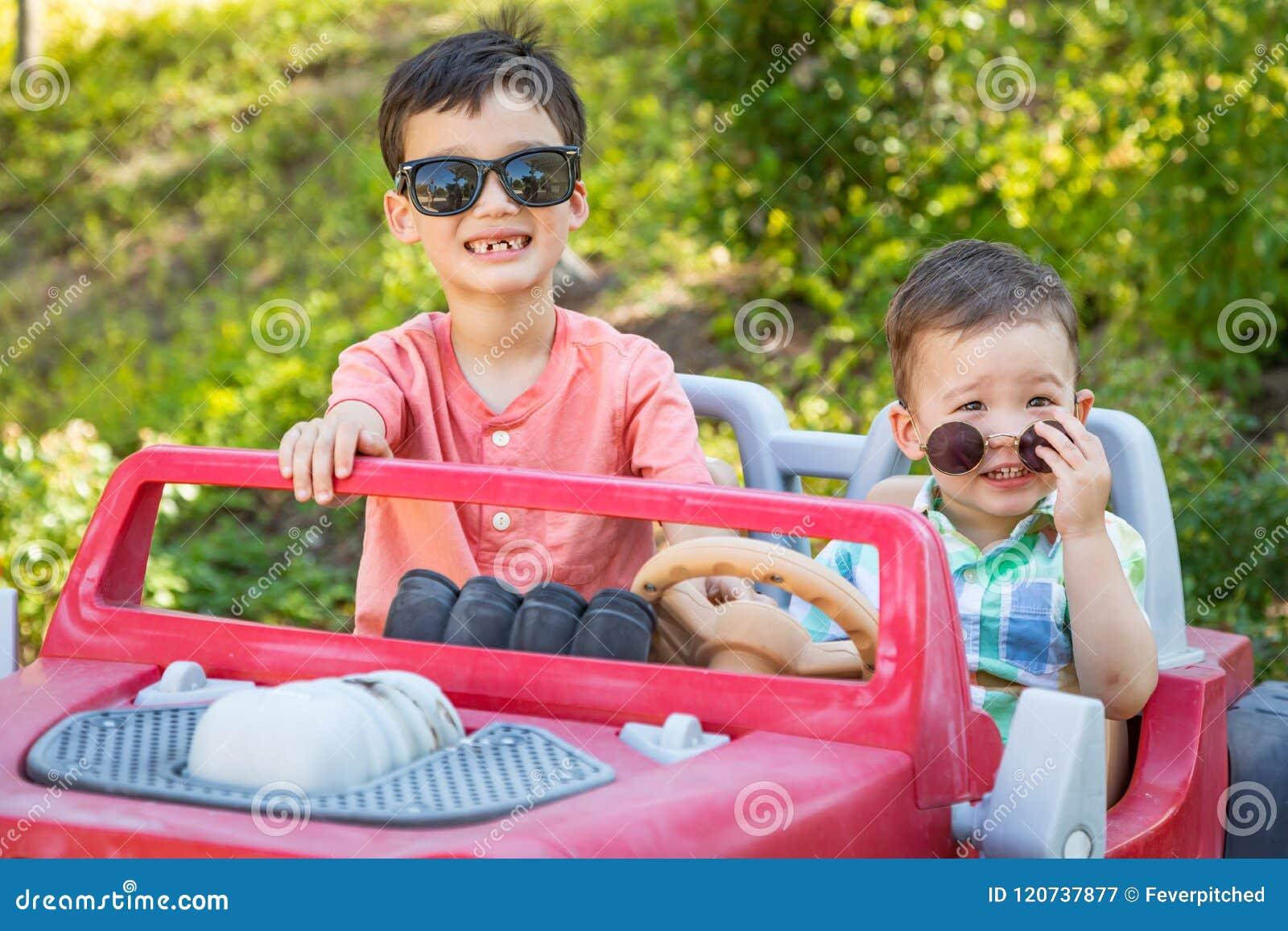 Giovane corsa mista cinese e fratelli caucasici che indossano gli occhiali da sole che giocano in Toy Car
