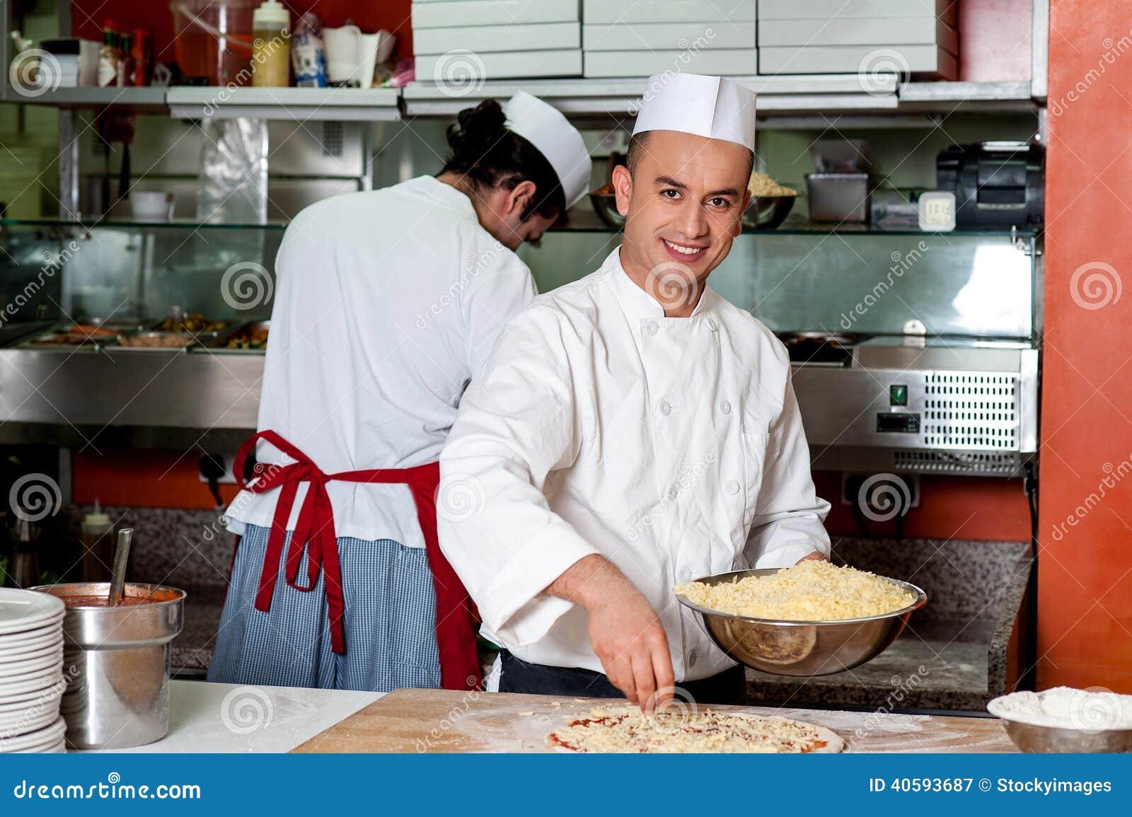 Giovane cuoco unico che produce pizza alla cucina