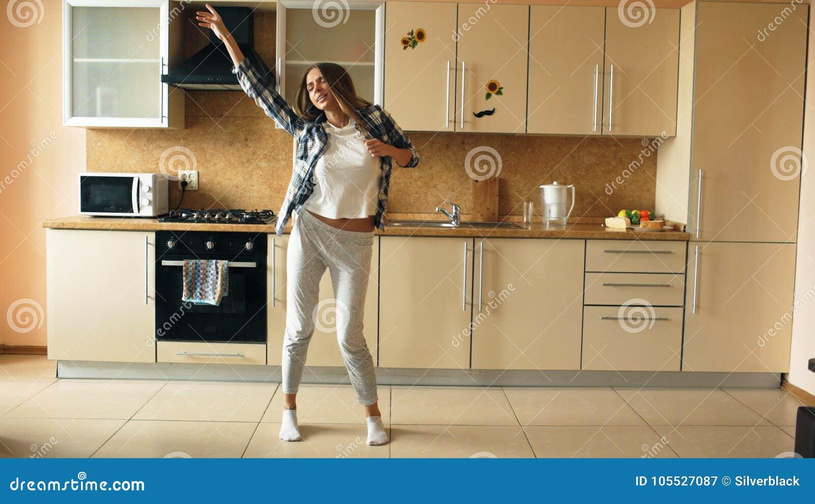 Giovane dancing divertente allegro e canto della donna con la siviera mentre avendo tempo libero nella cucina a casa