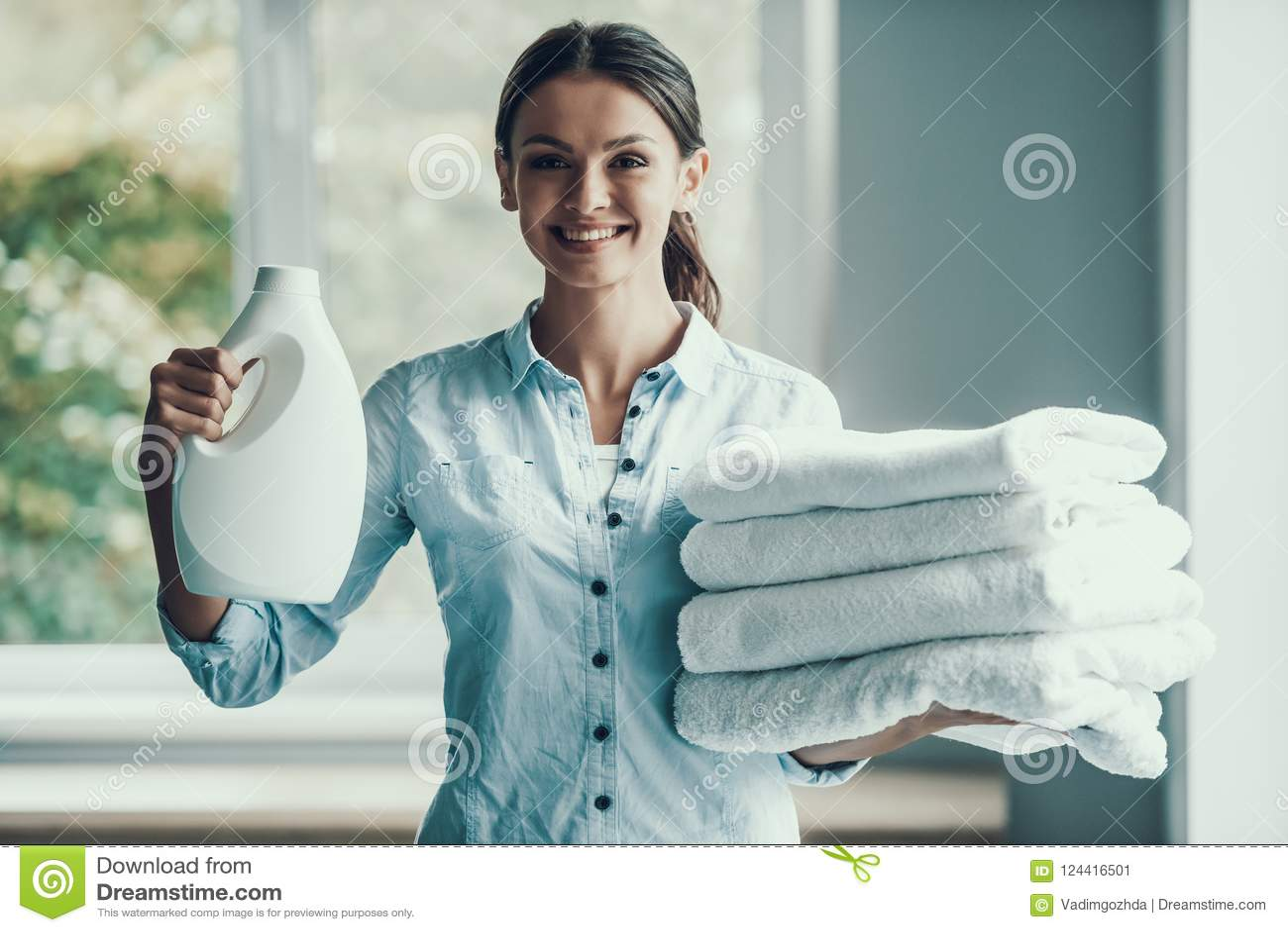 Giovane detersivo di lavanderia sorridente della tenuta della donna