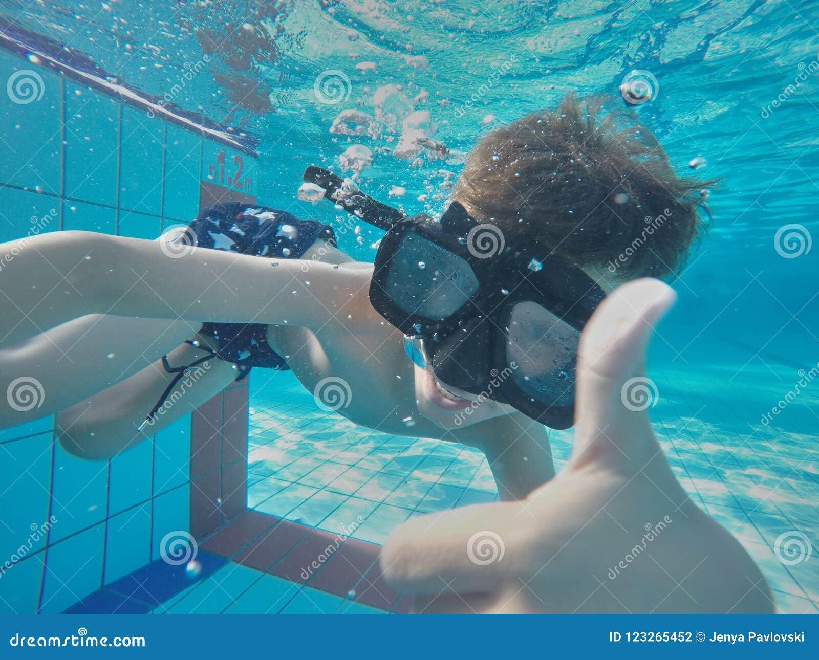 Giovane divertimento subacqueo del ragazzo nella piscina con gli occhiali di protezione Divertimento di vacanze estive