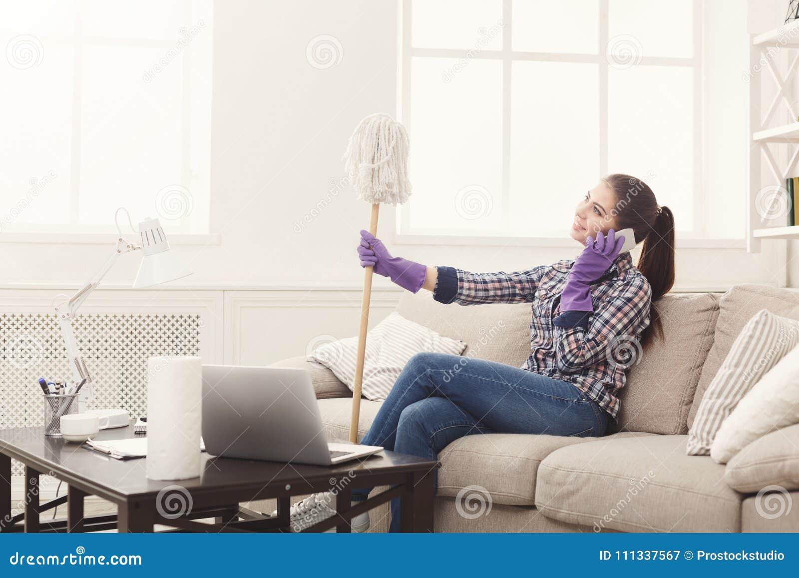 Giovane domestica che parla sul telefono durante la pulizia