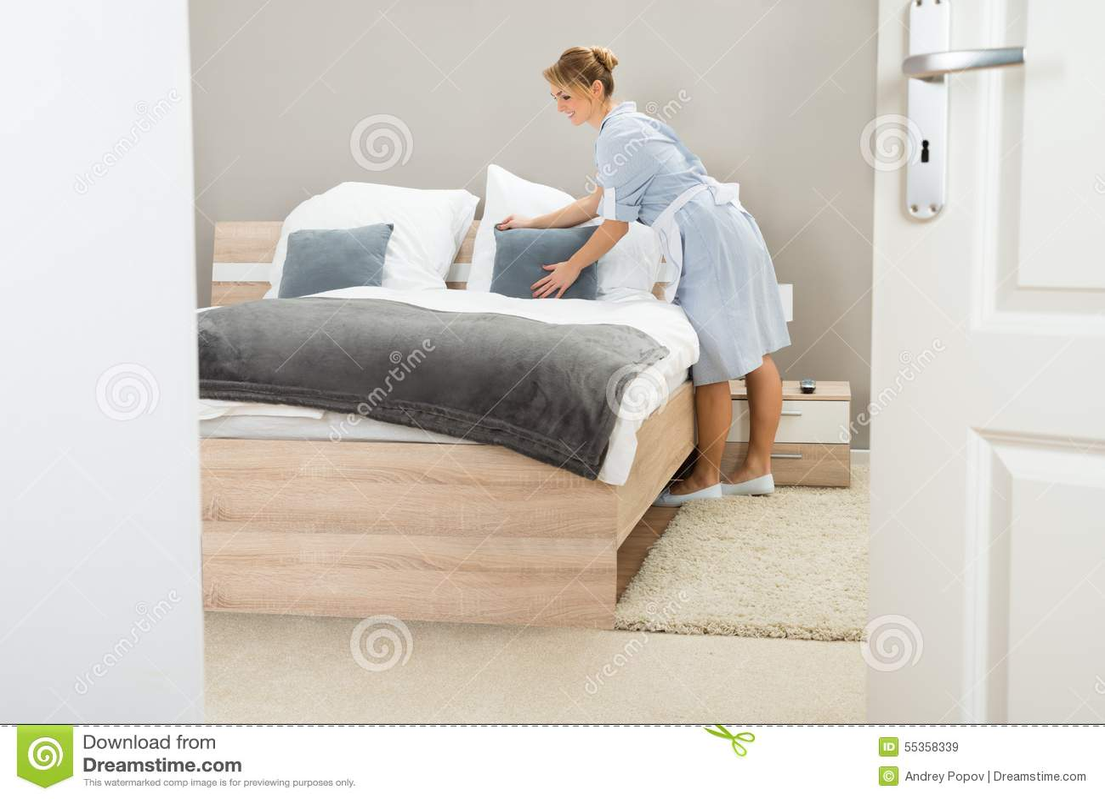 Giovane domestica che sistema cuscino sul letto