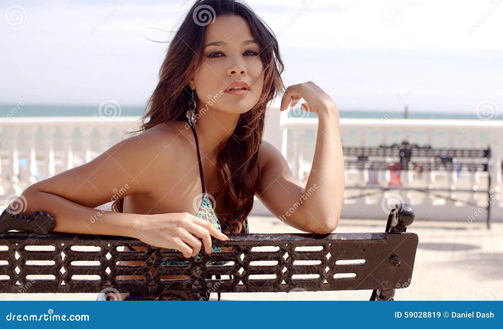 Giovane donna abbastanza felice che si rilassa alla spiaggia