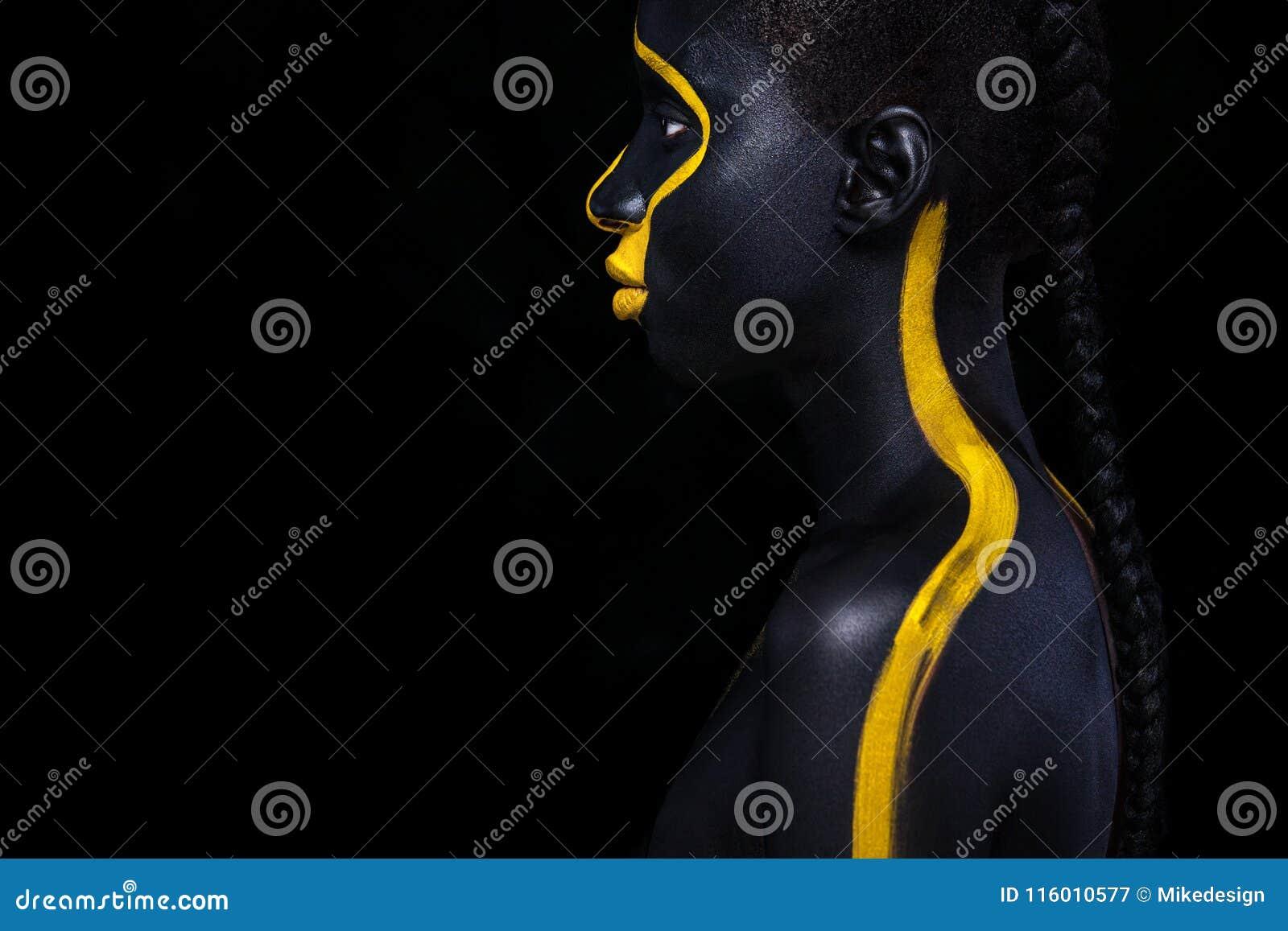 Giovane donna africana allegra con trucco di modo di arte Una donna stupefacente con trucco nero e giallo della pittura