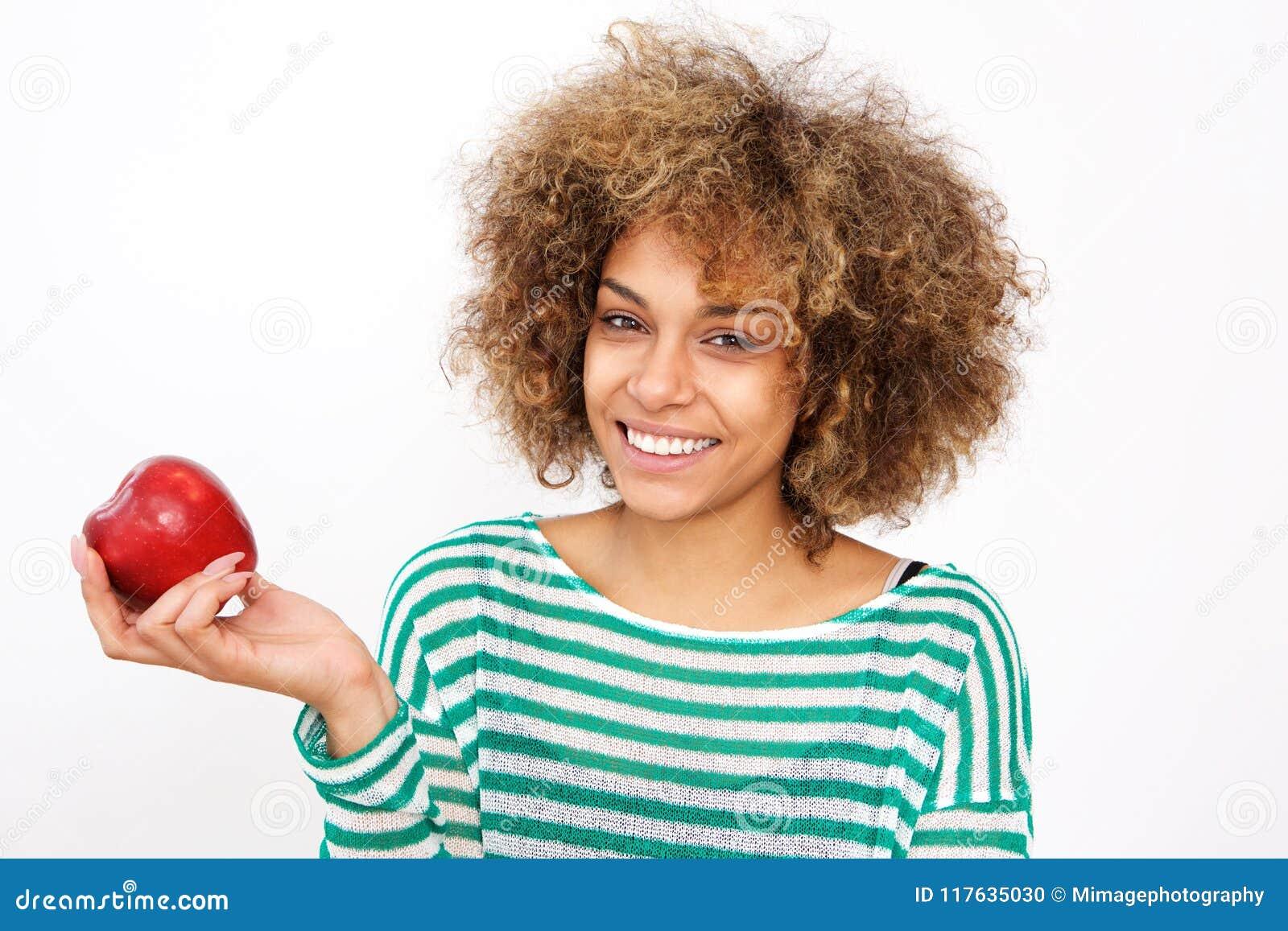 Giovane donna afroamericana attraente che tiene una mela