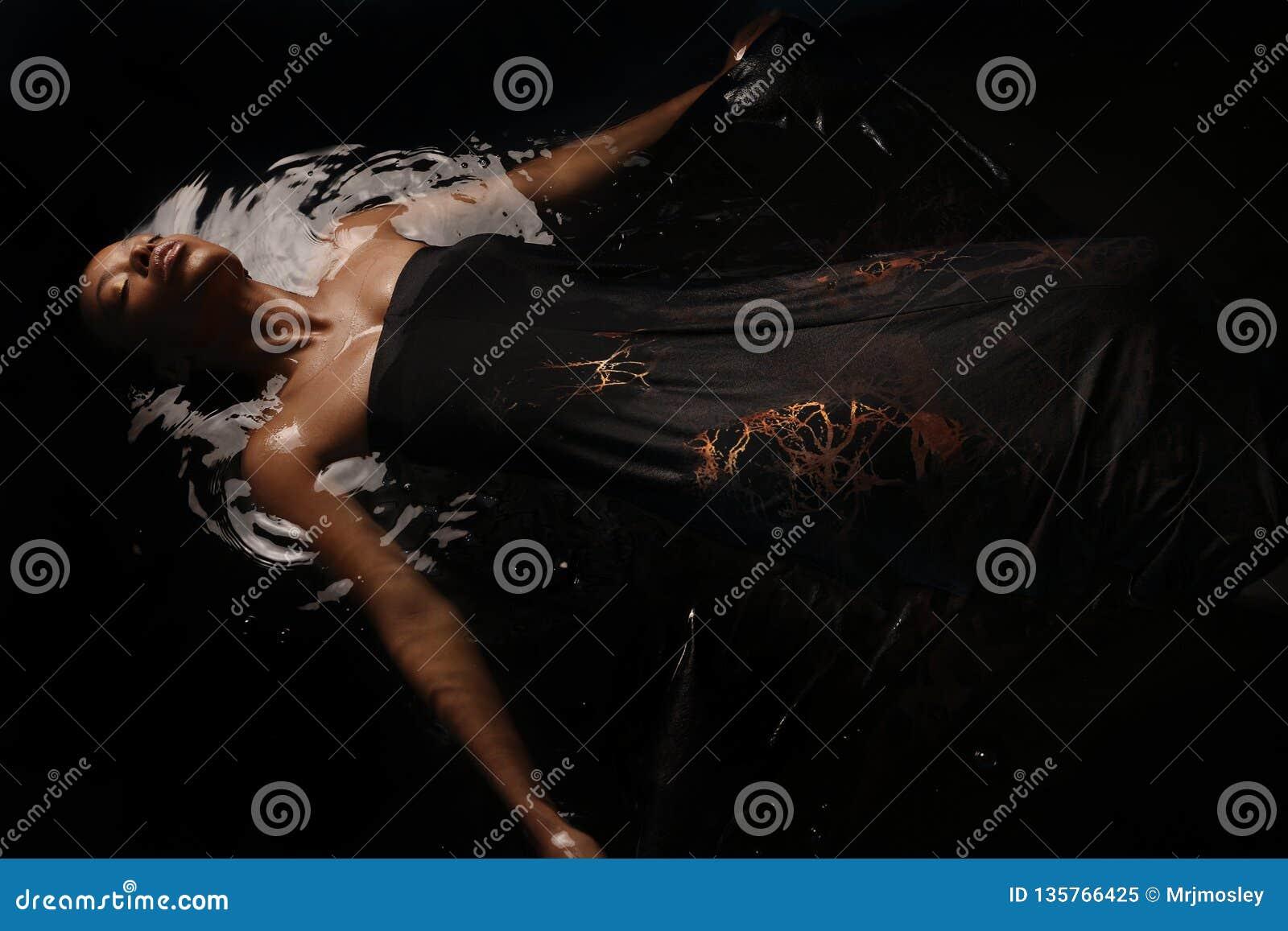 Giovane donna afroamericana che si trova in uno stagno di acqua