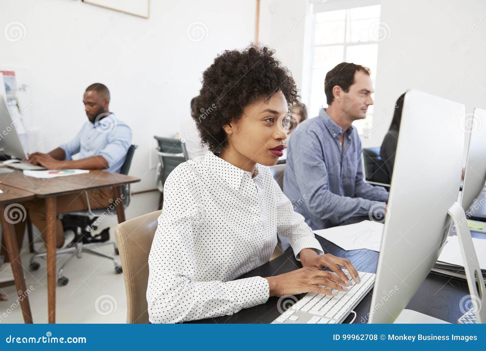 Giovane donna al computer con i colleghi in ufficio open space