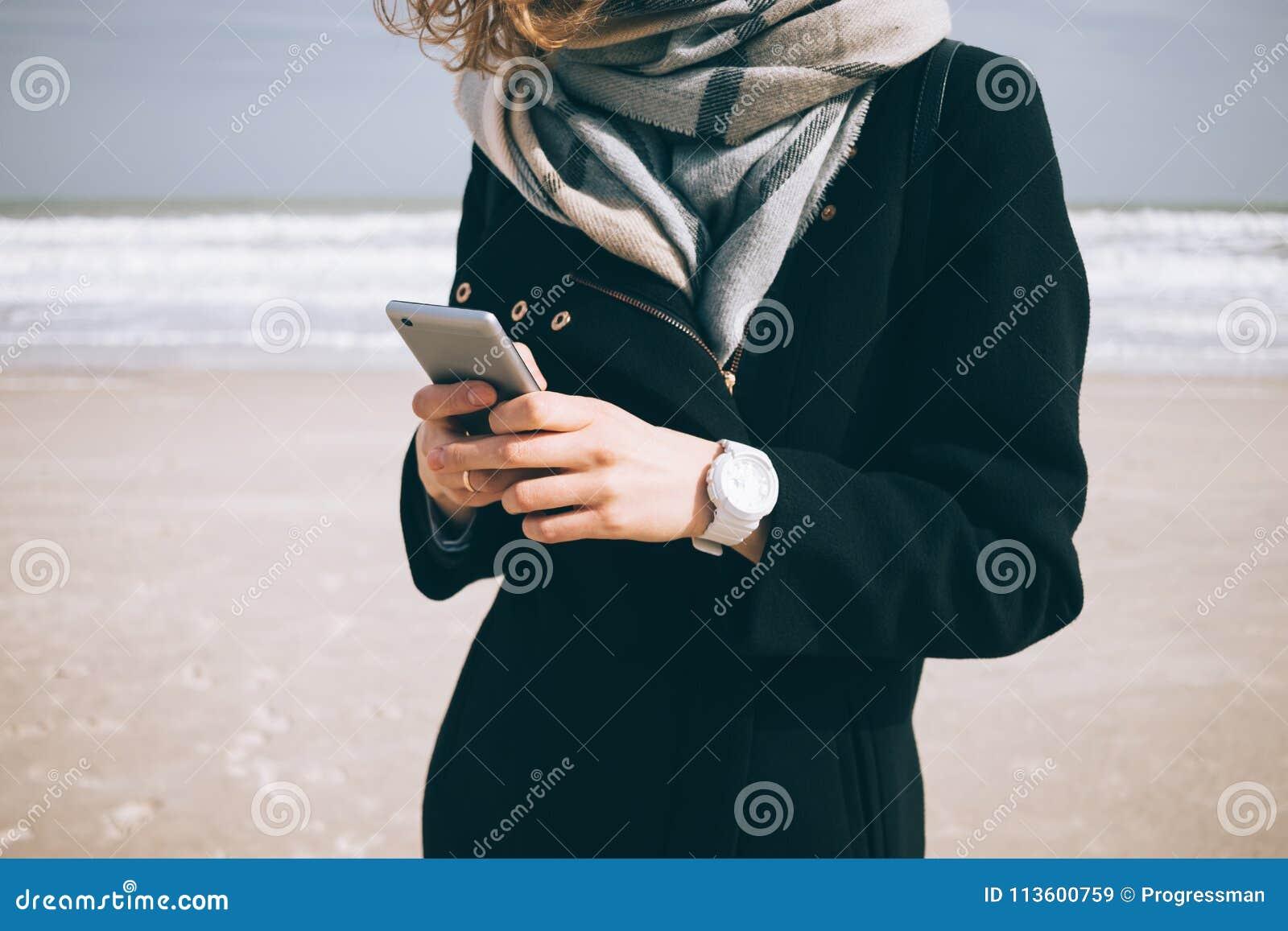 Giovane donna alla moda in cappotto e sciarpa