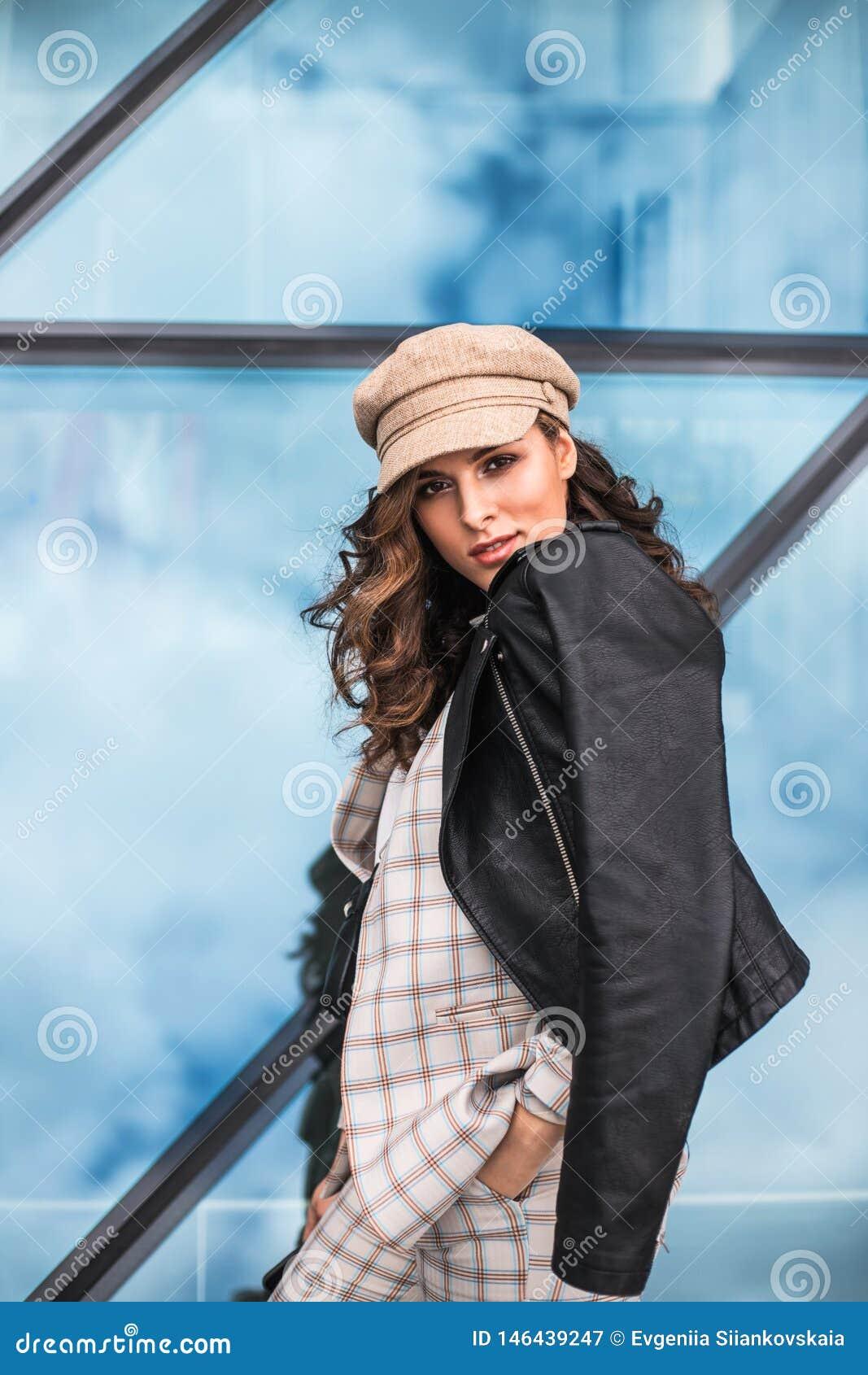 Giovane donna alla moda che posa contro le finestre di vetro all aperto