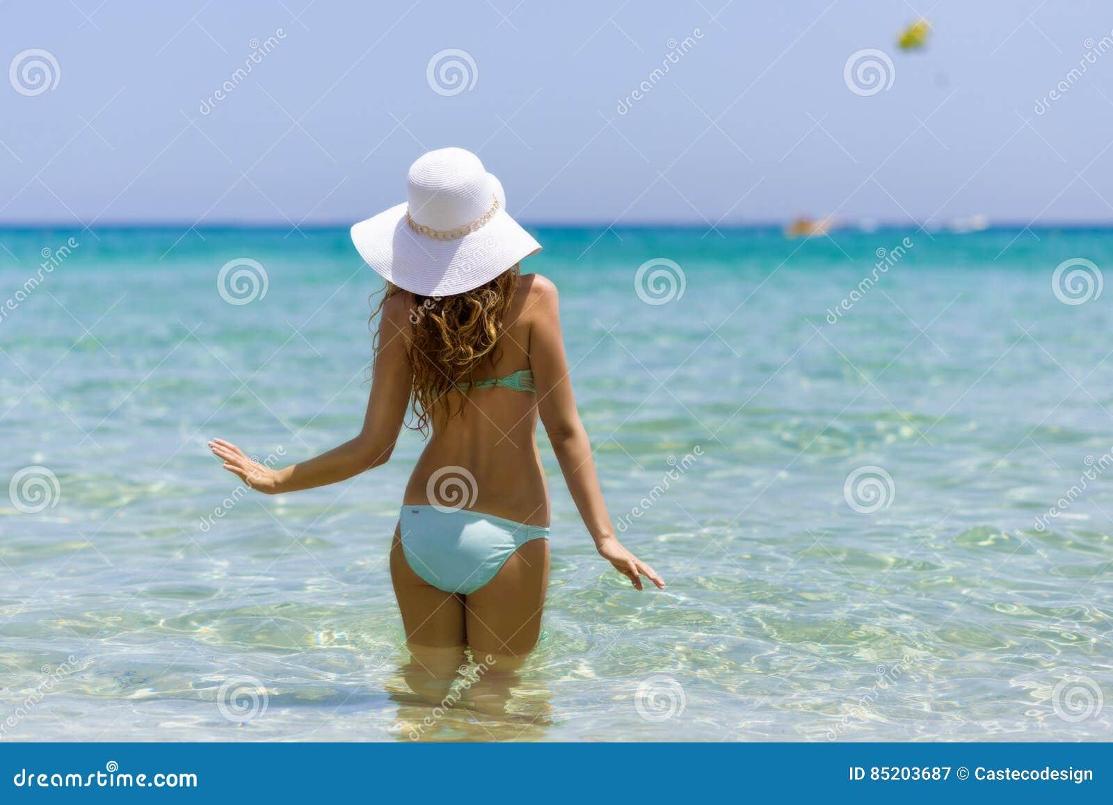 4c7b7b8126cc Giovane donna alla spiaggia Ritratto di una ragazza in cappello bianco  divertendosi nell acqua Bello mare di estate con acqua del turchese Vista  da dietro