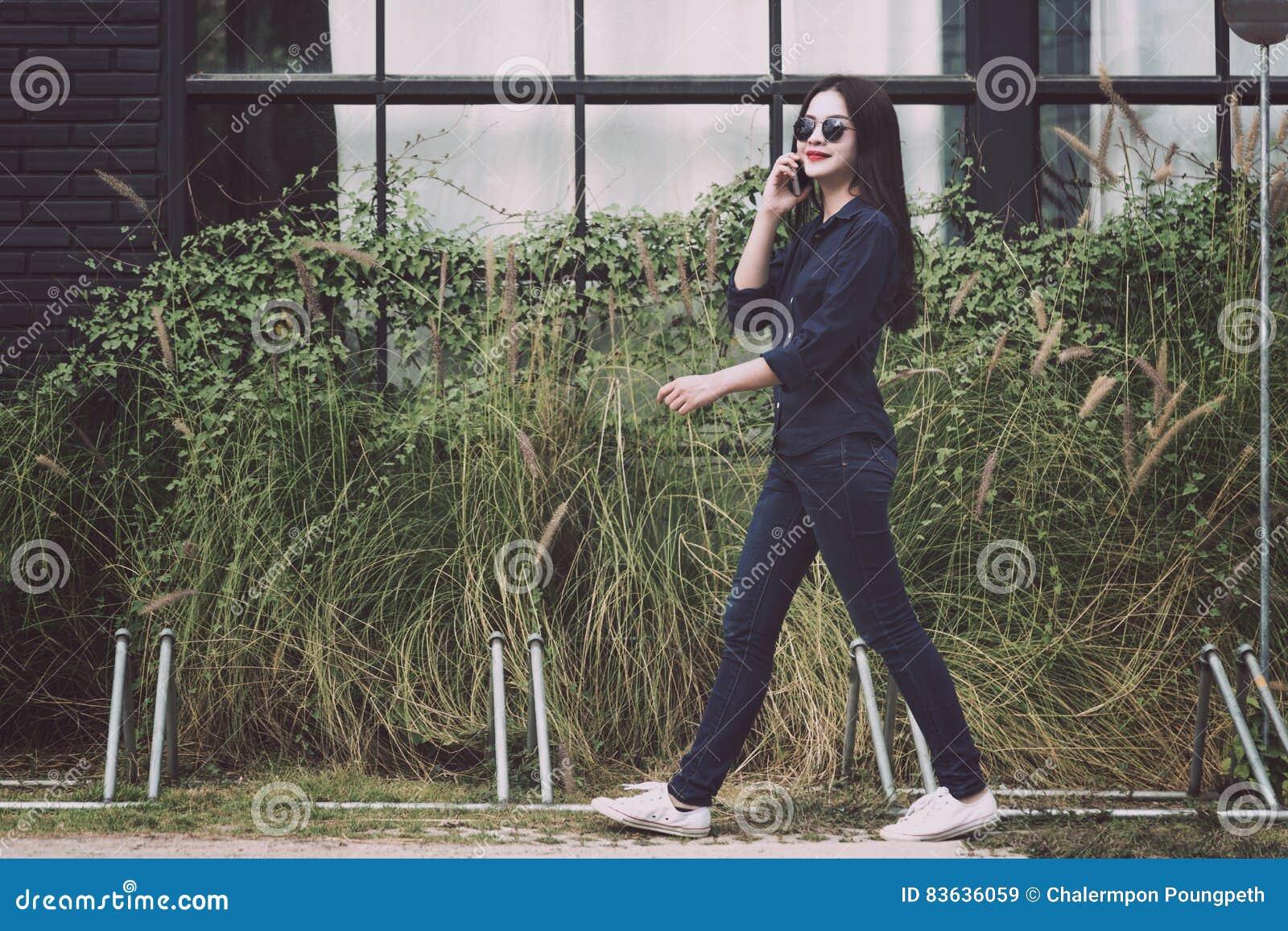 5ec6efa9cdba Giovane donna asiatica attraente che cammina e che parla con indifferenza  su lei