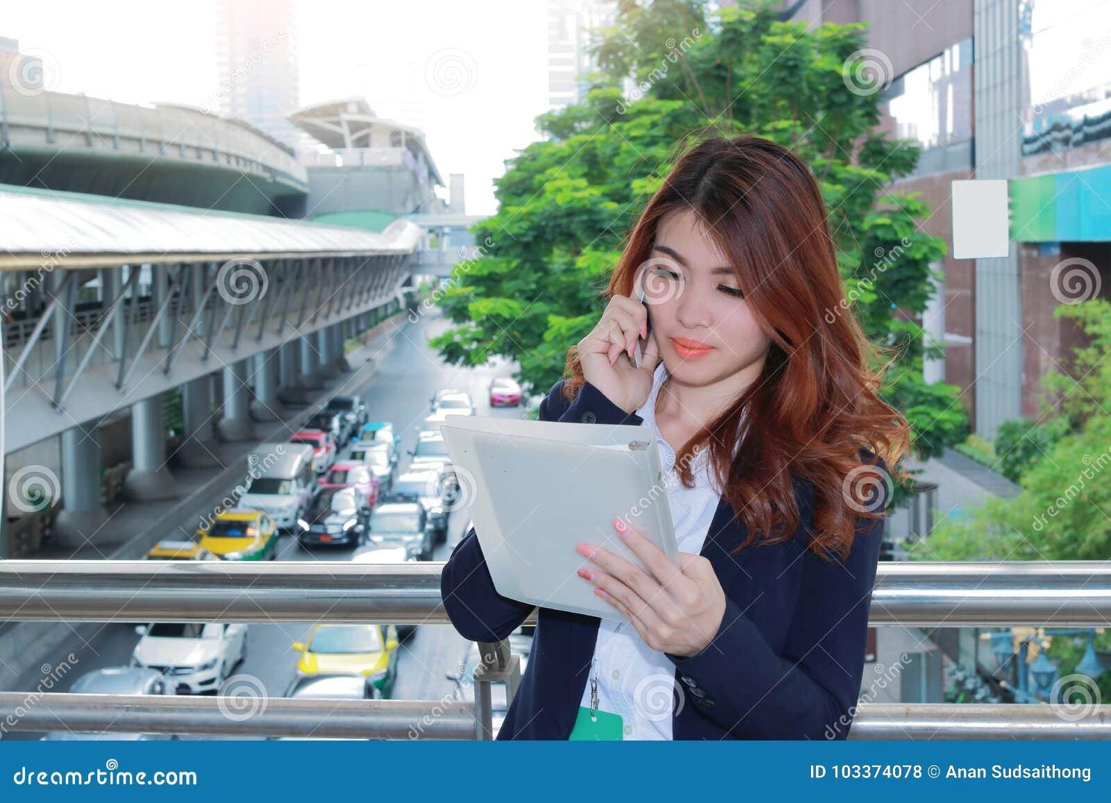 Giovane donna asiatica attraente di affari che parla sul telefono e che osserva gli archivi di documento in sue mani il fondo est
