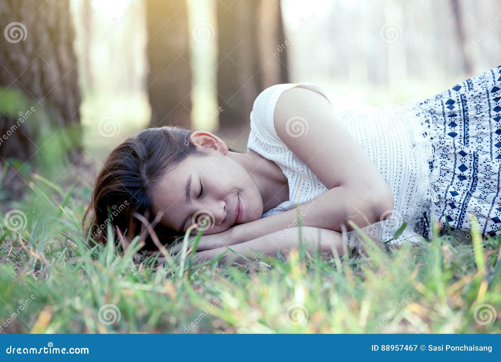 Giovane donna asiatica che dorme e che si riposa sull erba