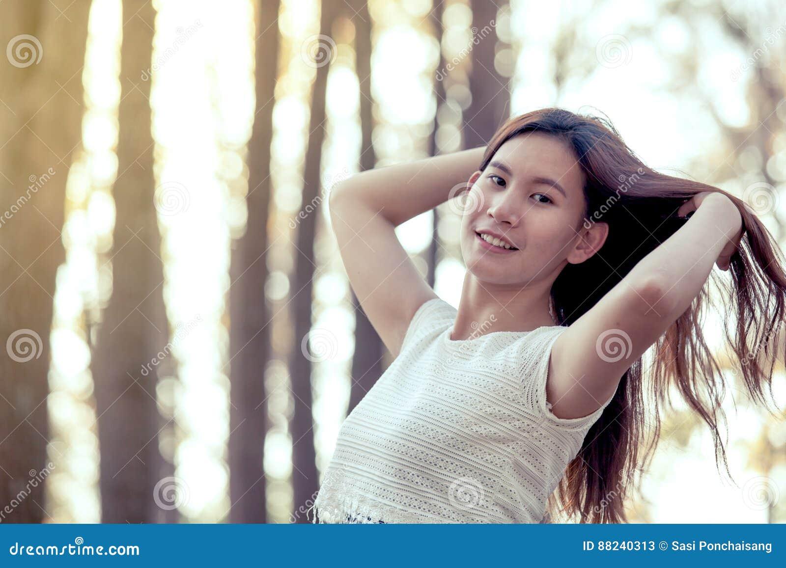 Giovane donna asiatica che passa rapidamente i suoi capelli e che gode della natura