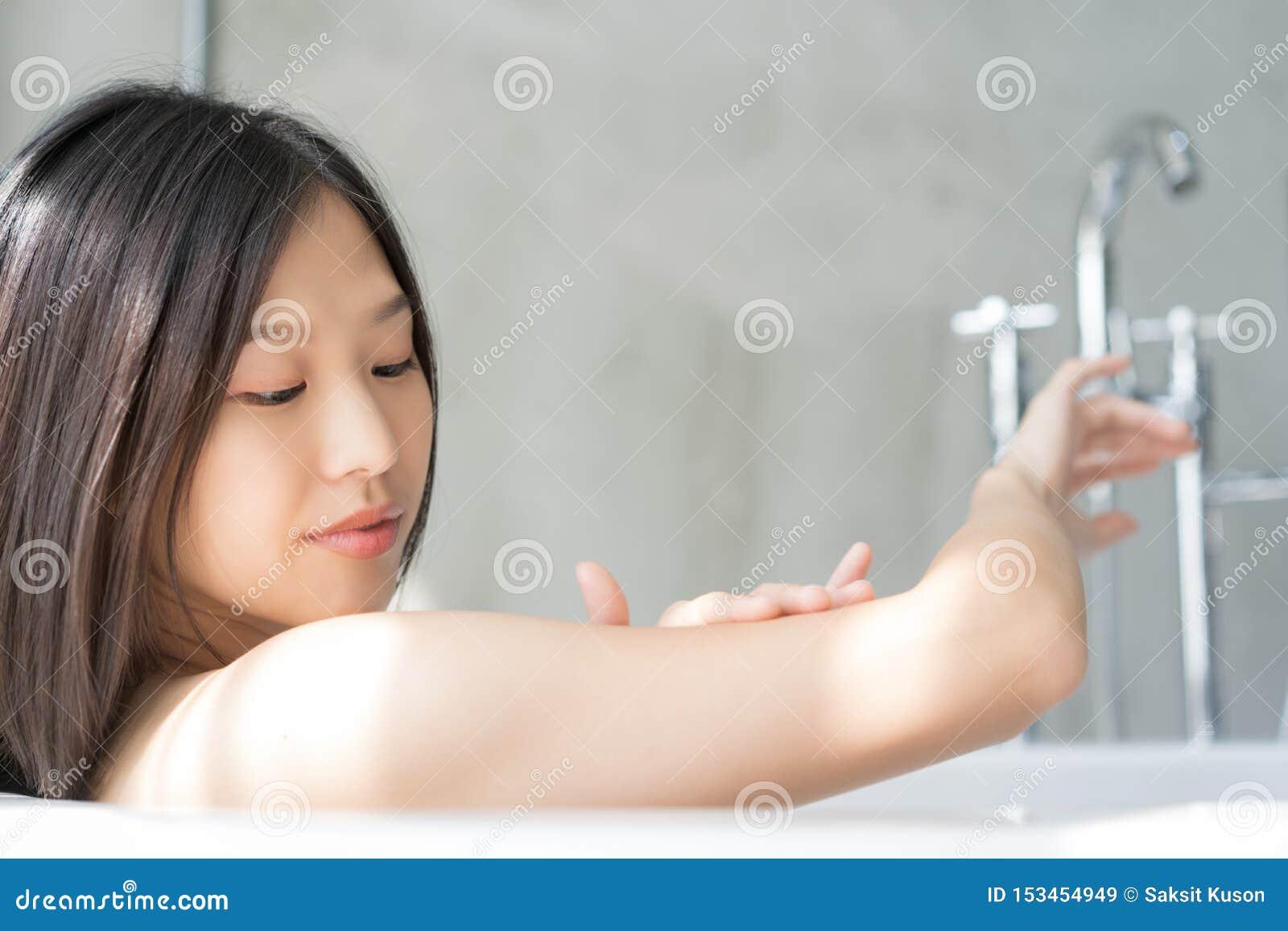 Giovane donna asiatica che si rilassa in un bagno Concetto femminile dello skincare