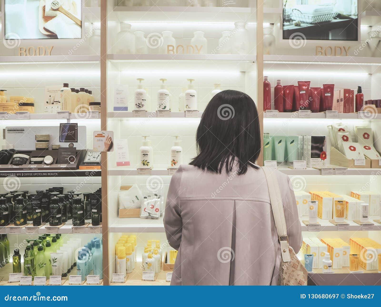 Giovane donna asiatica che sta dentro davanti ad uno scaffale con i prodotti dello skincare