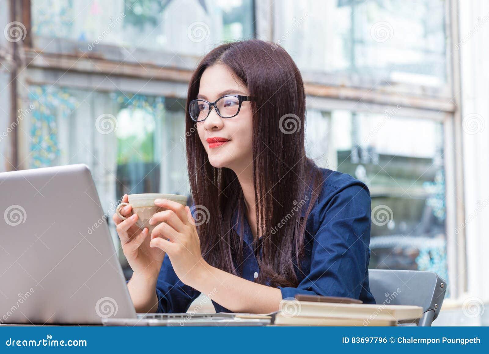 ce1c43584807 Giovane donna asiatica che tiene tazza di caffè e che prende una rottura da
